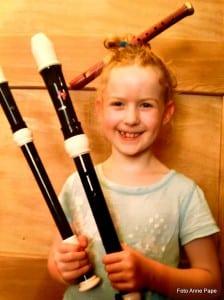 Lachendes Mädchen mit drei verschieden großen Blockflöten, Blockflötenunterricht - drei Flötengrößen