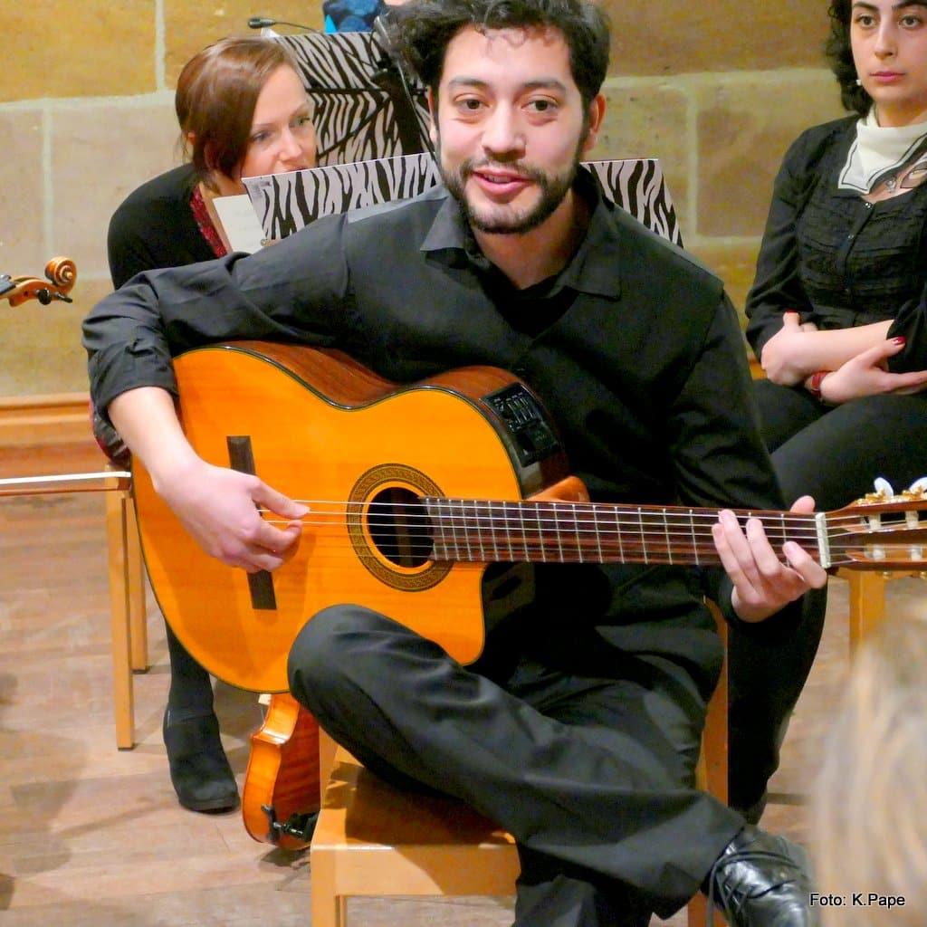Junger Mann, Gitarrenschüler, mit Gitarre im MusiCeum