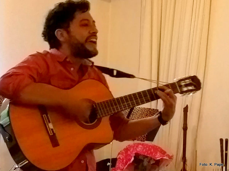 Junger Mann (Gitarrenschüler im MusiCeum) singt und spielt Gitarre
