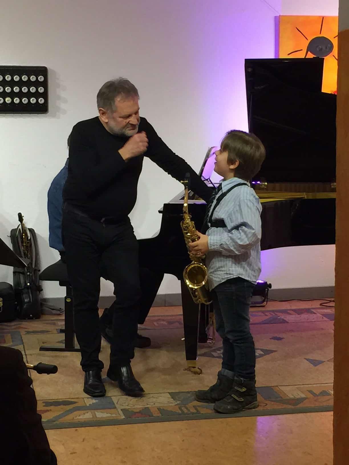 Junge mit Saxophon und Saxophonlehrer im MusiCeum