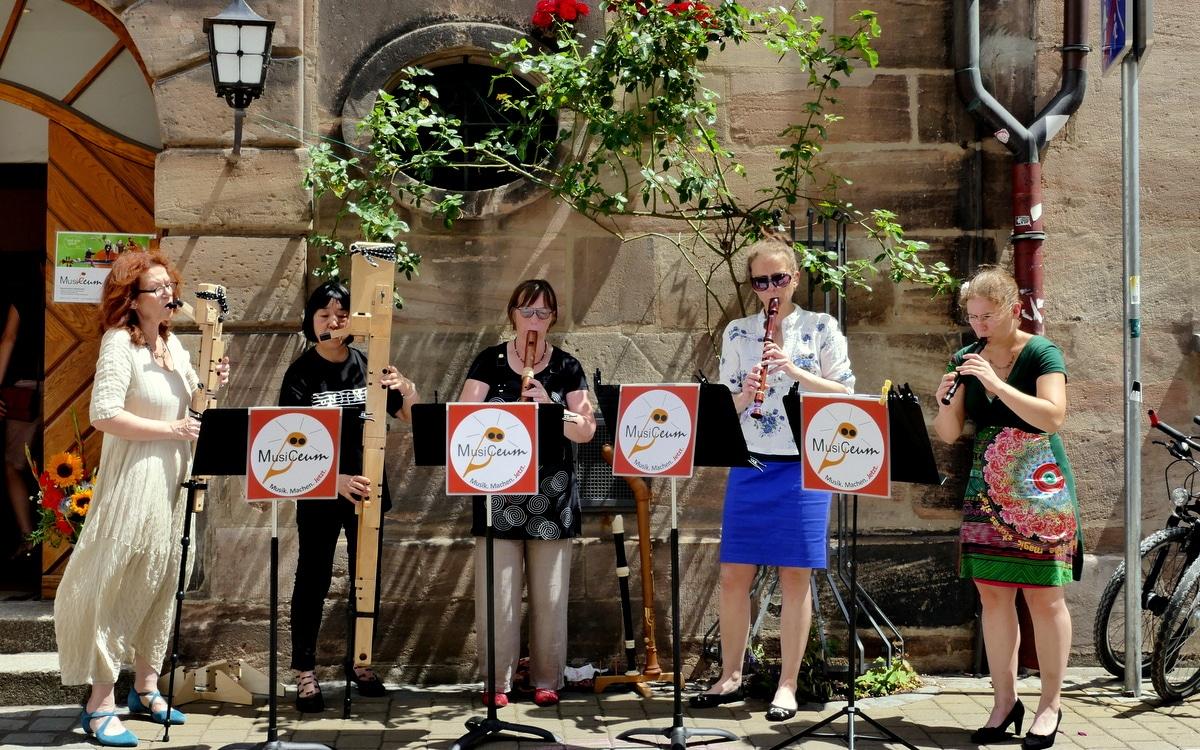 Blockflötenensemble Ltg. Anne Pape spielt vor historischem Gebäude, MusiCeum