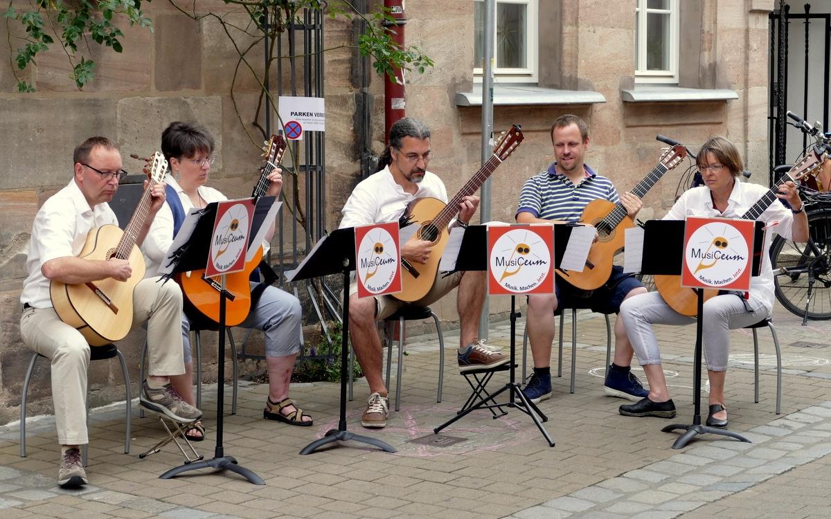 Fünf Gitarrenspieler vor historischem Gebäude, Musiceum