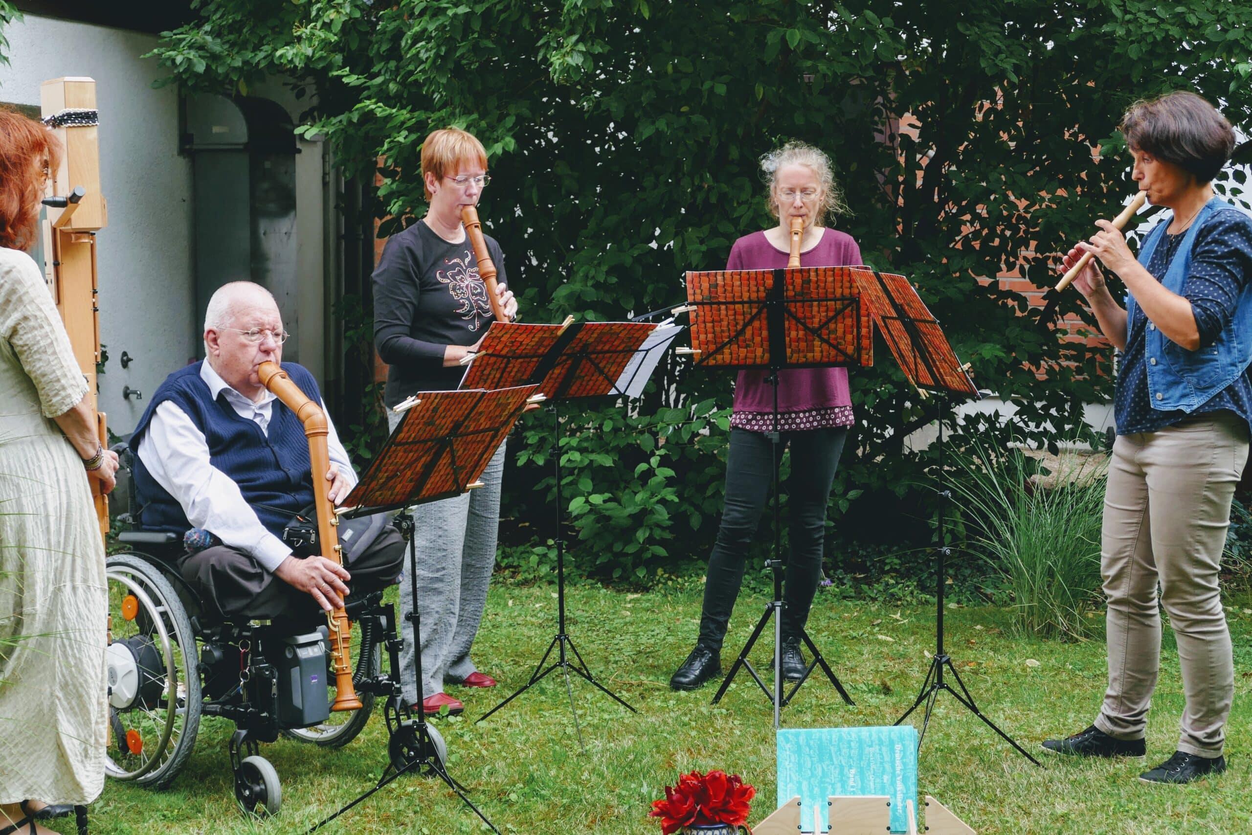 Fünf MusikerInnen mit Blockflöten und Rollstuhl