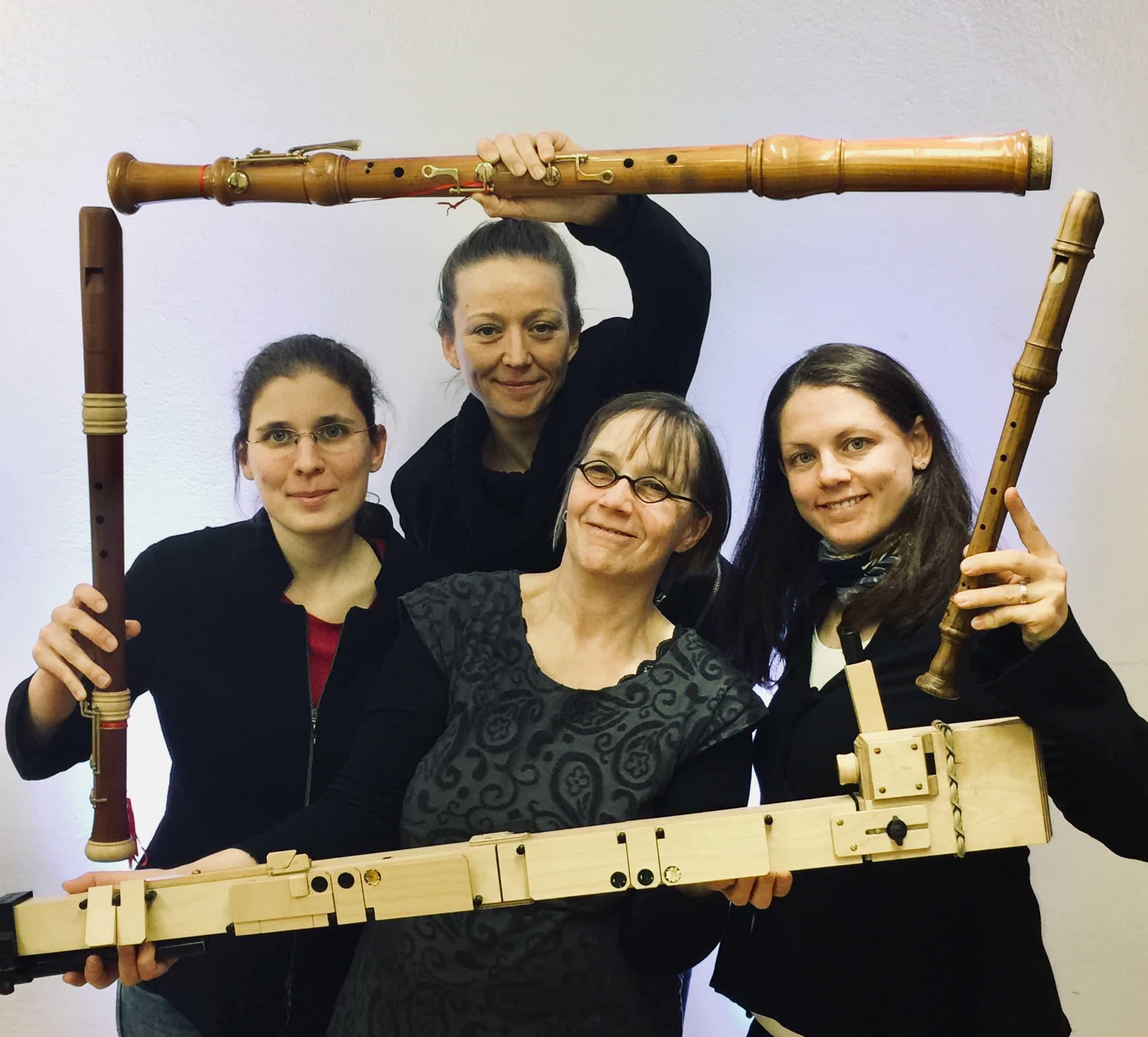 Vier Blockflötenspielerinnen schauen fröhlich durch einen Bilderrahmen aus blockflöten