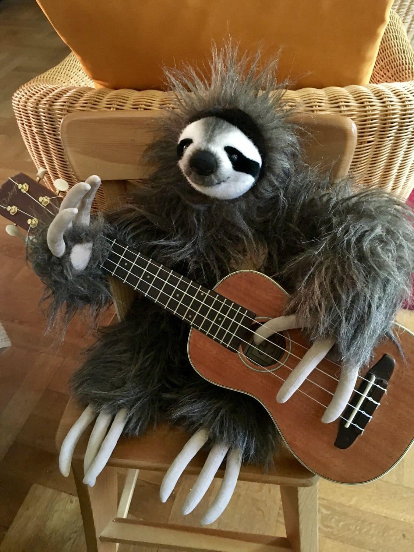 Faultier aus Plüsch macht Musik mit Ukulele